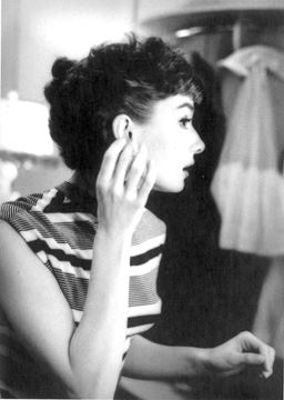 Picture of Audrey adjusts an earring as she gets ready to be photographed, 1953 © f22 foto space